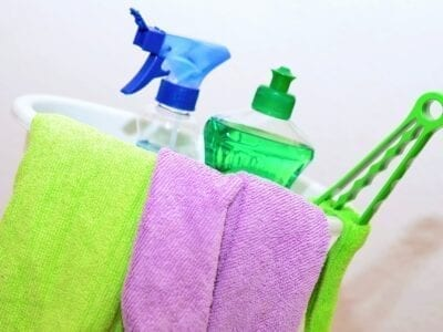 Cleaning bucket holding microfiber clothes and cleaning products.