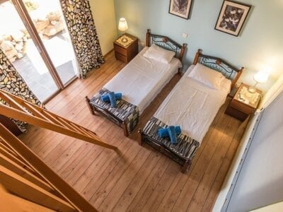 Bird's eye view of two twin beds in a hotel room with wooden floors.