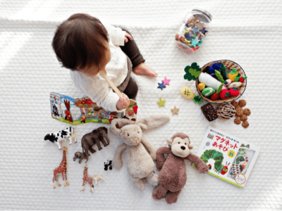 Bird's eye view of a baby with brown hair sitting on blanket surrounded by toys.