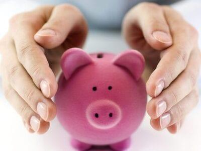 Close up photo of hands around a small pink piggy bank.