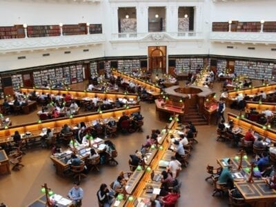 Photo of many people sitting at desks in a college library.