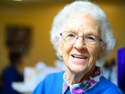 Close up photo of an elderly woman smiling.