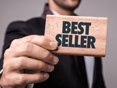 """Man holding small sign that says """"best seller."""""""