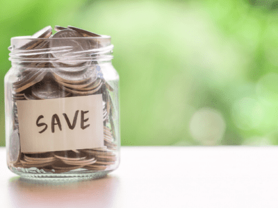 """Photo of glass jar filled with coins with label that says """"save."""""""
