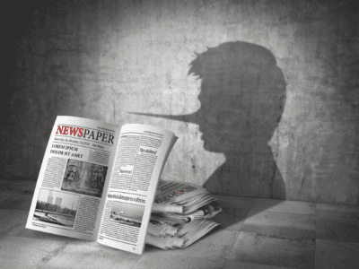 Graphic of newspapers with boy's shadow on the grey wall behind them.