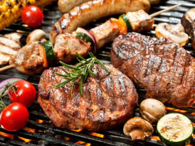 Photo of cooked steak and vegetables on a grill.