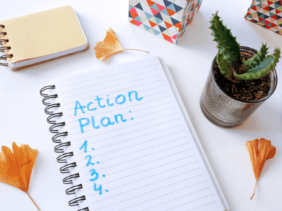 """Photo of lined paper with """"Action Plan"""" written on it, a pen, small cactus and dried ginkgo leaves."""