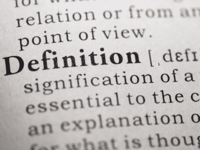 """Photo of the word """"definition"""" in a dictionary."""