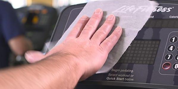 Hand wiping gym equipment.